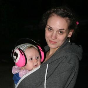 Frau mit kleinem Kind auf dem Arm, das Ohrenschützer trägt