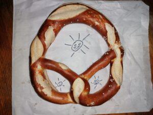 Laugenbrezel auf einer Papiertüte, auf die drei Sonnen gemalt sind, die durch die Öffnungen der Brezel hindurchscheinen
