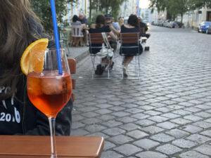 Glas mit Aperol Spritz auf einem Tisch auf der Straße